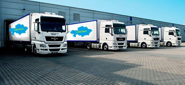 Четыре грузовика белого цвета с логотипом Turan Service